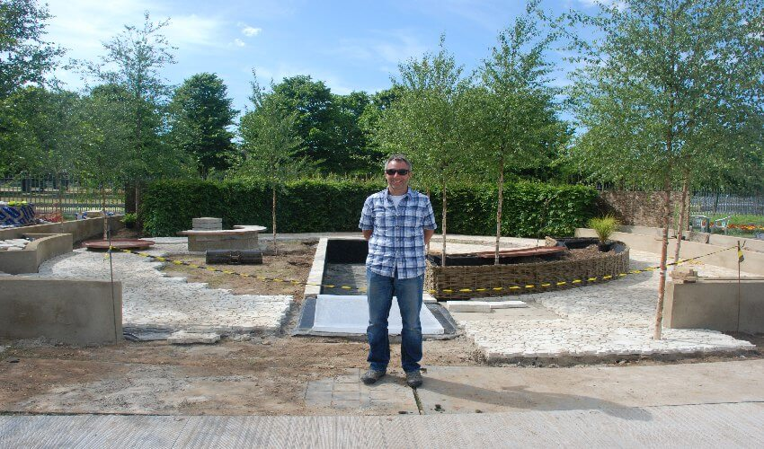 Simon Sutcliffe standing in the evolving garden at Hampton Court Flower Show