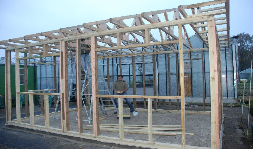 Member of staff standing in the middle of the wooden framework for the new office