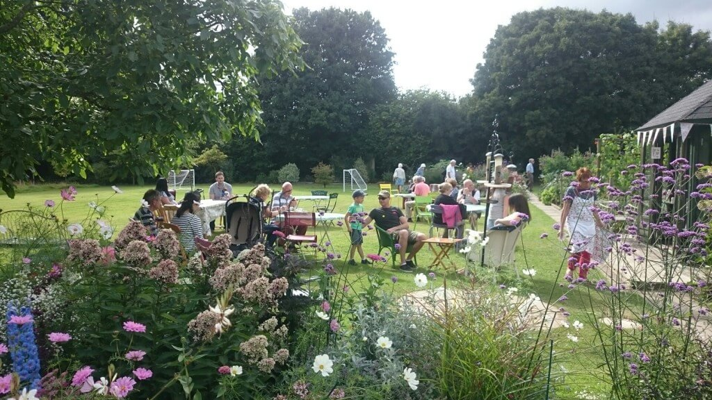 People drinking tea and eating cake on a sunny day in the nursery garden