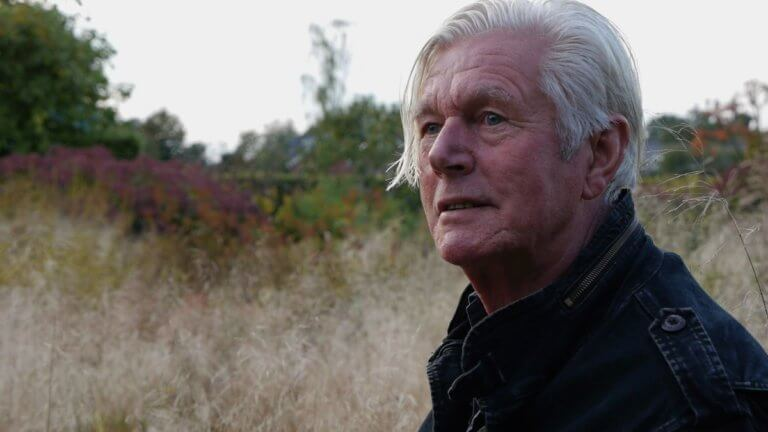 Photo of the designer Piet Oudolf with naturalistic planting in the background